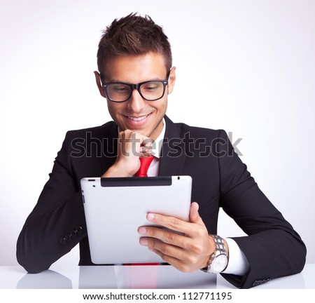 smiling young business man reading interesnting stuff on his electronic tablet pad - stock photo