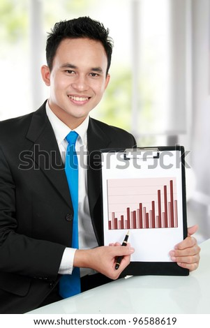 smiling young business man showing growth chart diagram - stock photo