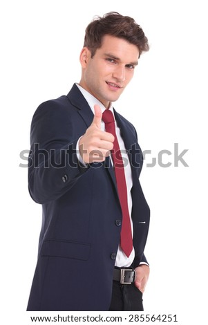 Smiling young business man showing the thumbs up gesture while holding his hand in pocket. - stock photo