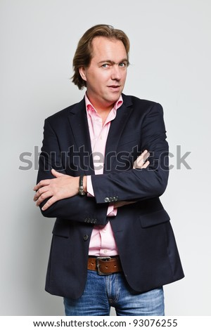 Smiling young business man with blond hair in blue suit and pink shirt isolated on white background - stock photo
