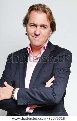 Smiling young business man with blond hair in blue suit and pink shirt isolated on white background
