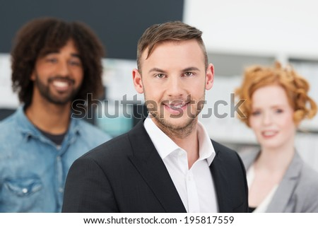 Smiling young business manager posing with members of his team standing behind him looking directly at the camera - stock photo