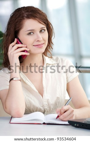 Smiling young business woman on phone taking notes in office - stock photo