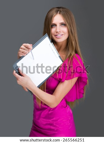 Smiling young business woman showing blank signboard, over gray background
