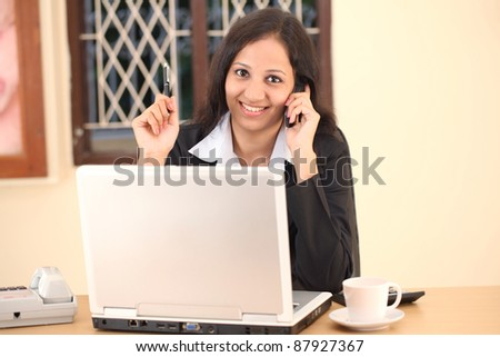 Smiling young business woman speaking on cellphone phone at work