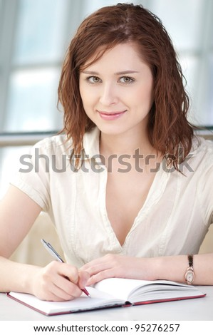 Smiling young business woman taking notes in office - stock photo
