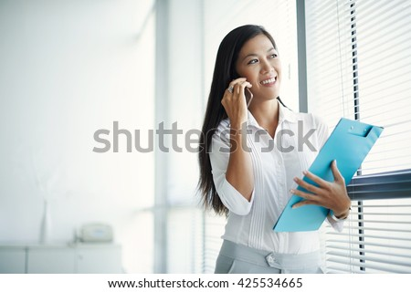 Smiling young business woman talking on phone