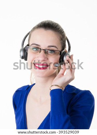 Smiling young business woman wearing a headset answering calls at a client service center or wanting to communicate hands free while continuing to work in her office - stock photo