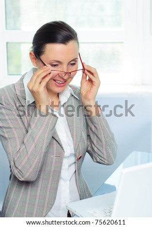 smiling young business woman with glasses using laptop