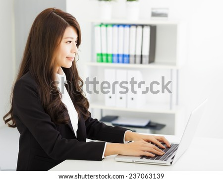 smiling young business woman working with  laptop - stock photo