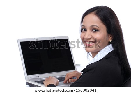 Smiling young business woman working with laptop against white - stock photo