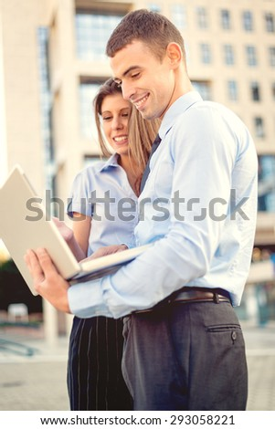 Smiling young businessman and businesswoman in front of office building looking at the laptop, while from behind the sun shines.