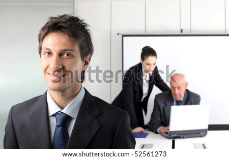 Smiling young businessman and two business people working on the background - stock photo