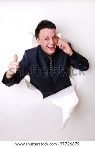 smiling young businessman break through a paper wall - stock photo