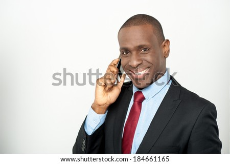 Smiling young businessman communicating through cellphone - stock photo