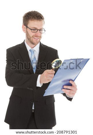 Smiling young businessman examining document on clipboard with magnifying glass over white background - stock photo