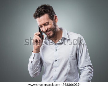 Smiling young businessman having a phone call with his mobile