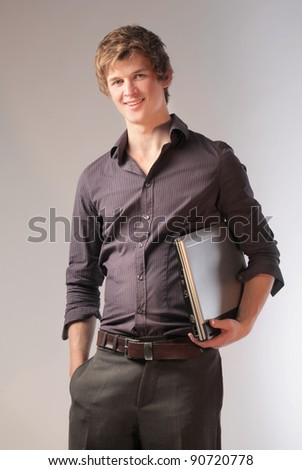 Smiling young businessman holding a laptop - stock photo