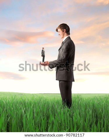 Smiling young businessman holding an older one on a green meadow - stock photo