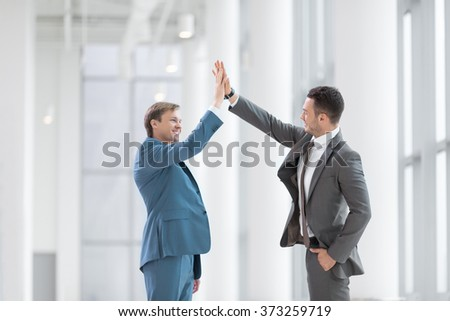 Smiling young businessman in office - stock photo