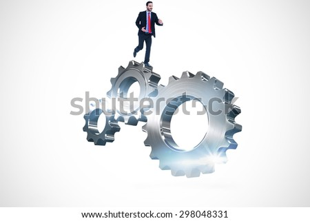 Smiling young businessman in suit running against metal cog and wheel connecting - stock photo
