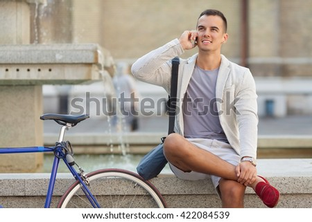 Smiling young businessman is sitting at a fountain and talking on the mobile phone while his bicycle is standing beside him - stock photo