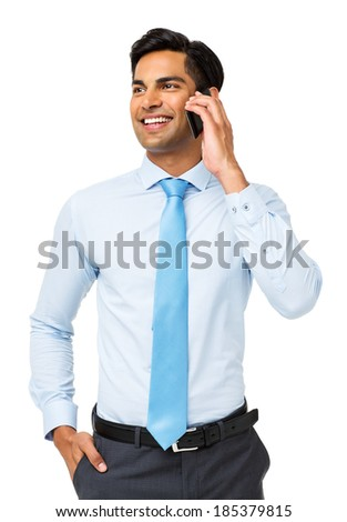 Smiling young businessman looking away while using smart phone over white background. Vertical shot. - stock photo