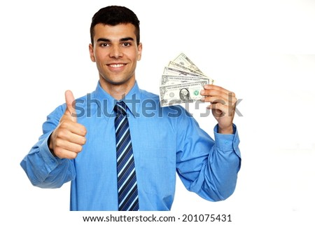 Smiling young businessman man in blue shirt shows you money and thumbs up - stock photo