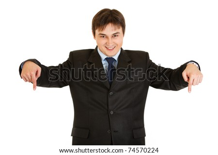 Smiling young  businessman pointing down isolated on white