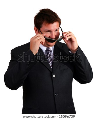 Smiling young businessman putting on  sunglasses - stock photo