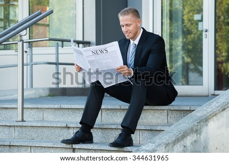 Smiling Young Businessman Reading Newspaper Sitting On Stairs