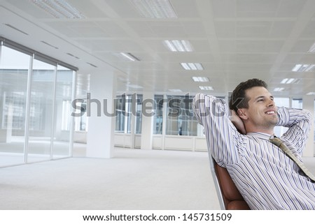 Smiling young businessman relaxing on chair in empty office space - stock photo