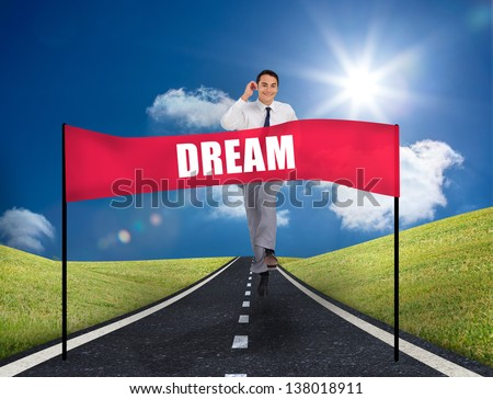 Smiling young businessman running on a road with a banner with dream written on it - stock photo