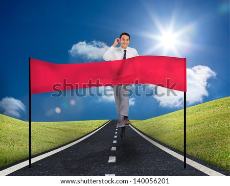 Smiling young businessman running on a road with copy space banner in front of him
