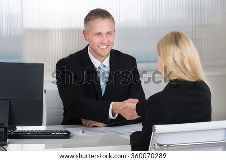 Smiling young businessman shaking hands with female candidate at desk in office - stock photo