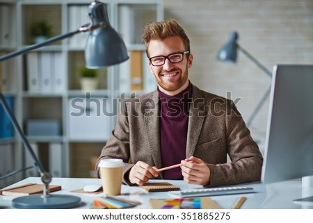 Smiling young businessman sitting at his workplace and smiling - stock photo