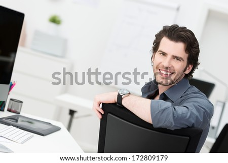 Smiling young businessman sitting in his office turning to look at the camera over the back of his chair - stock photo
