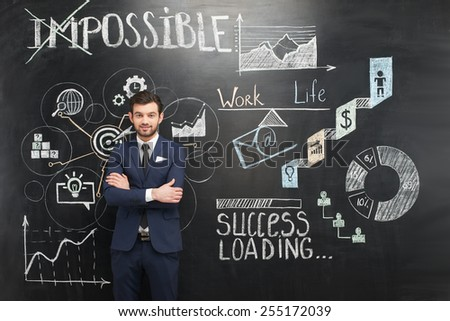 Smiling young businessman standing on dark chalkboard background. Colorful symbols and graphs painted on it. Concept for successful project