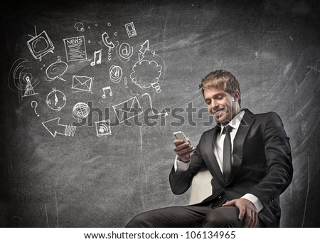 Smiling young businessman using a mobile phone with symbols beside him