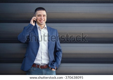 Smiling young businessman using a smart phone in front of the modern office building - stock photo