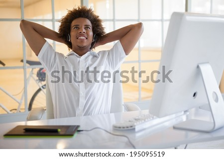 Smiling young businessman using digitizer and headset at desk in his office - stock photo