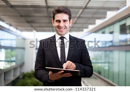 Smiling young businessman using his digital tablet at the office - stock photo