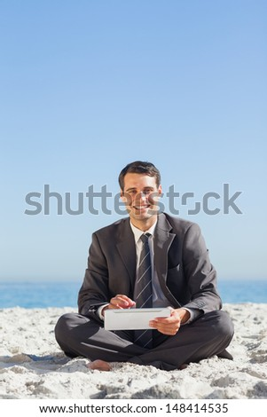 Smiling young businessman using his tablet computer on the beach - stock photo