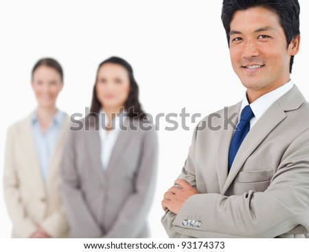 Smiling young businessman with colleagues behind him against a white background