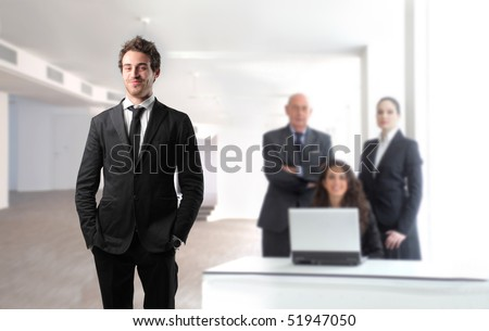 Smiling young businessman with group of business people on the background - stock photo