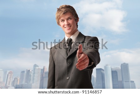 Smiling young businessman with thumbs up and cityscape in the background - stock photo