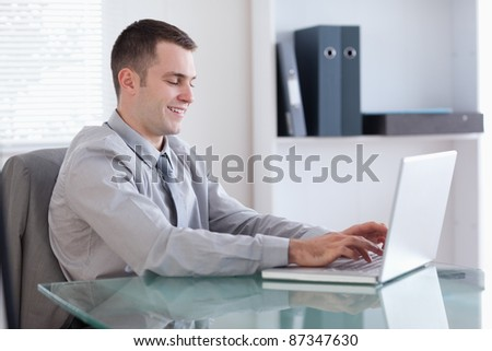 Smiling young businessman working on his laptop