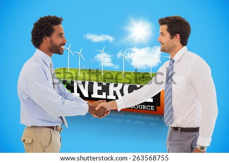 Smiling young businessmen shaking hands in office against wind turbine field in an energy saving battery - stock photo