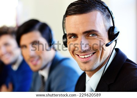 Smiling young businesspeople and colleagues in a call center office - stock photo