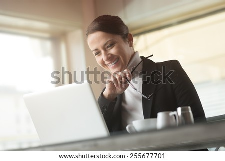 Smiling young businesswoman at the bar working on her laptop - stock photo